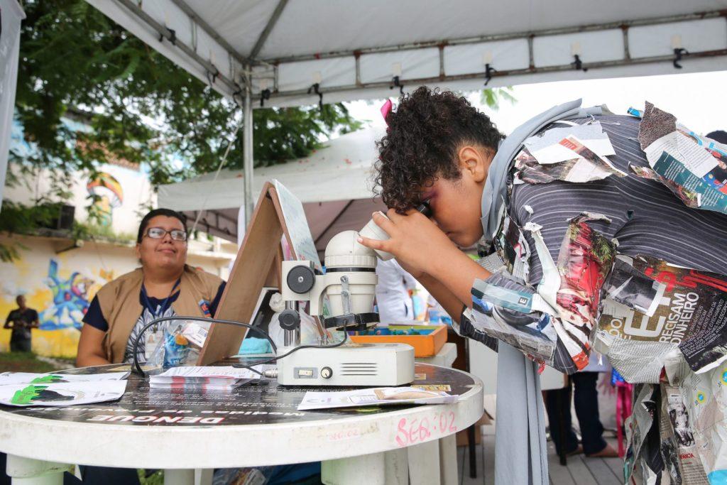 Aluno da rede municipal observa a evolução do mosquito da dengue no laboratório montado na praça