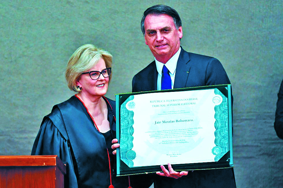 Brazilian President-elect Jair Bolsonaro displays a diploma that certifies he can take office as president, next to Electoral Supreme Court (TSE) president Justice Rosa Weber during a ceremony at the TSE in Brasilia, on December 10, 2018. Bolsonaro takes office on January 1, 2019.   / AFP / EVARISTO SA