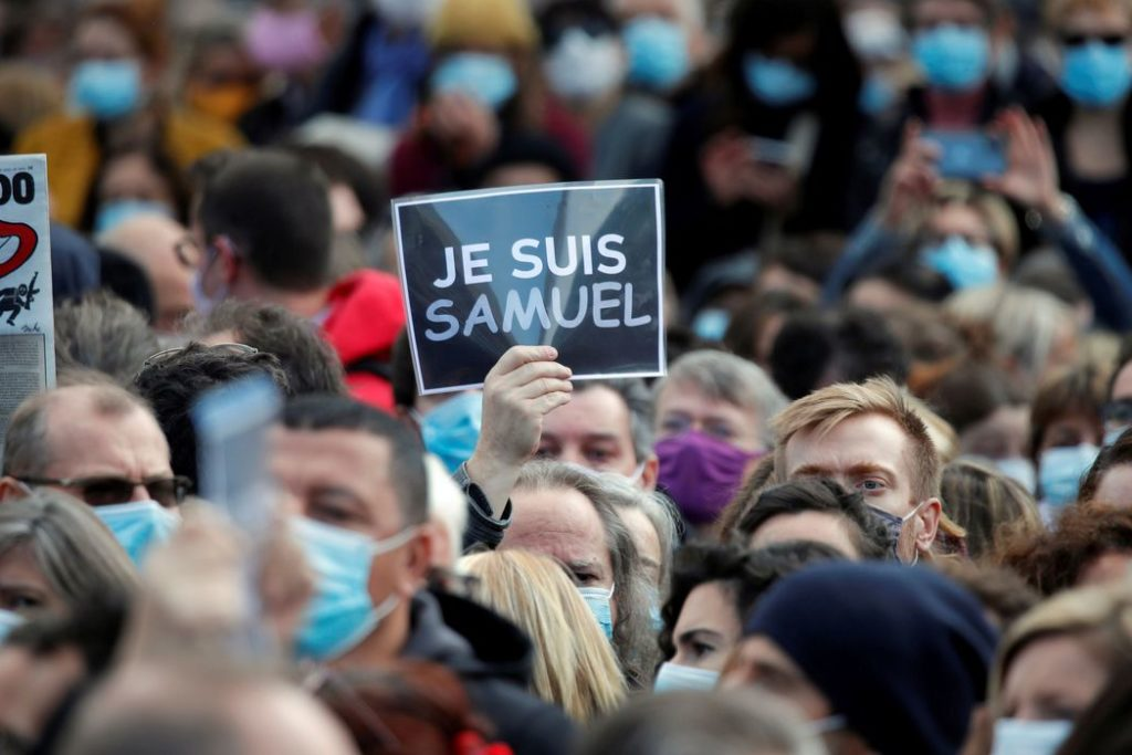 "People gather at the Place de la Republique in Paris, to pay tribute to Samuel Paty, the French teacher who was beheaded on the streets of the Paris suburb of Conflans-Sainte-Honorine, France, October 18, 2020. Placard reads ""I am a Samuel"". REUTERS/Charles Platiau"
