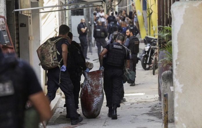 Policiais retiram um dos mortos na operação/Ricardo Moraes/Reuters