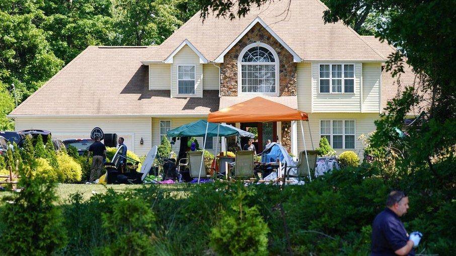 Casa em Nova Jersey onde aconteceu a festa e o tiroteio; policiais investigam o local na manhã de domingo (23)/Matt Rourke/AP Photo