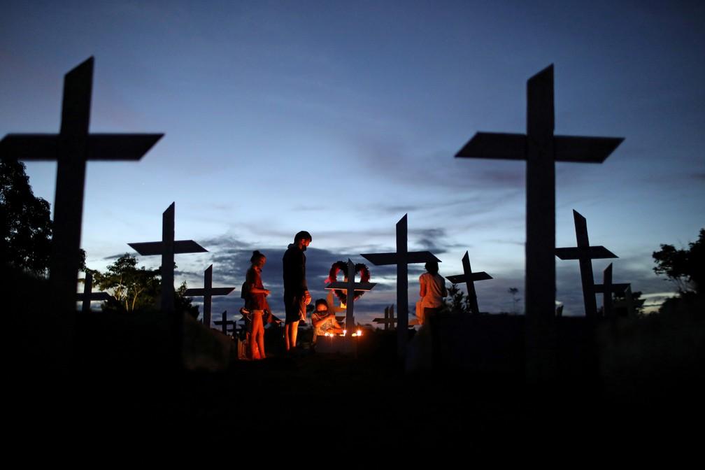 Parentes rezam sobre o túmulo de ente querido morto pela Covid/Bruno Kelly/Reuters