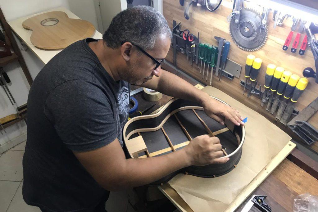Davi Lopes faz acabamento em um dos instrumentos feitos por ele/Divulgação/Governo do RJ