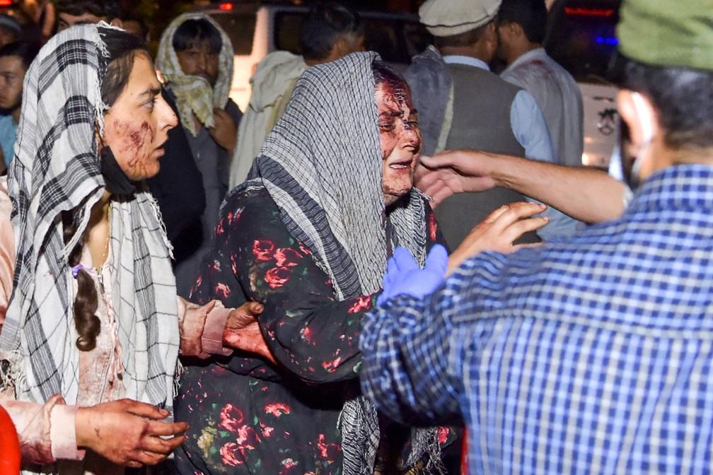 Mulheres feridas chegam a um hospital para tratamento após duas explosões no aeroporto de Cabul/Wakil Kohsar/AFP