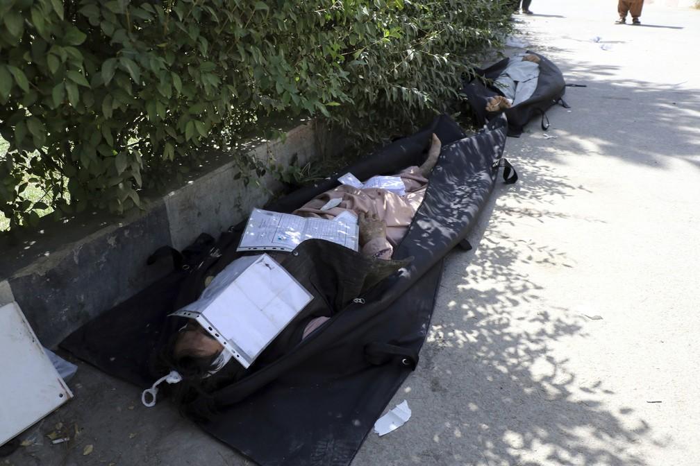 Corpos de afegãos mortos no atentando são colocados no chão em um hospita/Wakil Kohsar/AFP