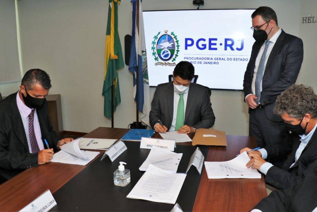 O procurador-geral do Estado, Bruno Dubeux (c); o controlador-geral do RJ, Jurandir Lemos Filho; e o presidente da Carioca Engenharia, Eduardo Backheuser na assinatura do acordo/Divulgação/Governo do Rio